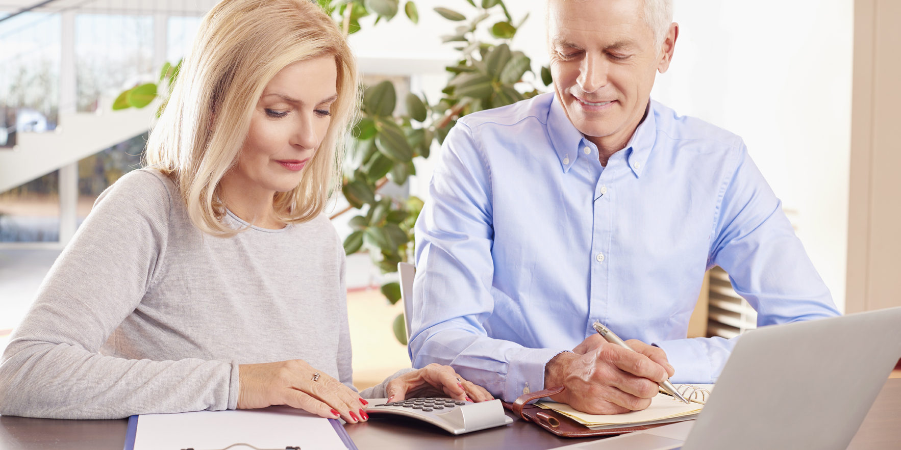 Shot of an older couple sitting at home in front of laptop and manage their monthly budget.